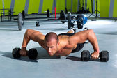 Gym man push-up strength pushup exercise with dumbbell — Stock Photo