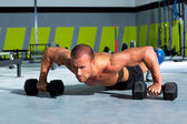 Gym man push-up strength pushup exercise with dumbbell — Stockfoto