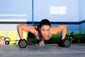 Flexiones de fuerza gimnasio mujer push-up con mancuerna — Foto de Stock