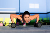 Gym woman push-up strength pushup with dumbbell — Stock Photo