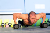Gym man push-up strength pushup with dumbbell — Stock Photo