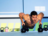 Gym man push-up strength pushup with Kettlebell — Stock fotografie