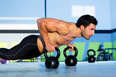 Gym man push-up strength pushup with Kettlebell — Zdjęcie stockowe