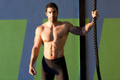 Crossfit gym man holding hand a climbing rope — Stock Photo