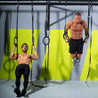 Stock Photo: Crossfit dip ring two men workout at gym dipping