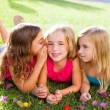 Children girls playing whispering on flowers grass — Stock Photo