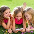 Children friend girls playing internet with smartphone - Stock Photo