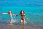 Children girls friends running together in the beach shore — Stock Photo