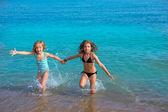 Children girls friends running together in the beach shore — Stock Photo
