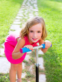 Child happy girl playing with scooter in garden — Stock Photo