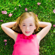 Blond kid girl lying on garden grass smiling aerial view — Stock Photo #18420327
