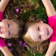 Children friend girls lying on garden grass smiling — Stock Photo