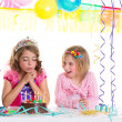 Children happy girls blowing birthday party cake — Stock Photo