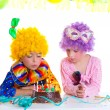 Children birthday party clown wigs blowing cake candles - Stock Photo