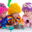 Children birthday party clown wigs blowing cake candles — Stock Photo #18422567