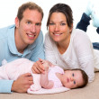 Stock Photo: Baby mother and father happy family lying on carpet
