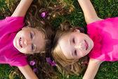 Children friend girls lying on garden grass smiling — Stock Photo