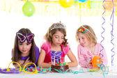 Children happy girls blowing birthday party cake — Stock Photo