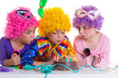 Children birthday party clown wigs blowing cake candles — Stock Photo