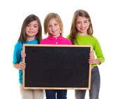 Children girls group holding blank blackboard copy space — Stock Photo