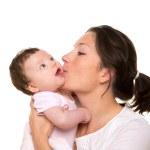 Beautiful mother kissing baby girl hug on white — Stock Photo #18430111