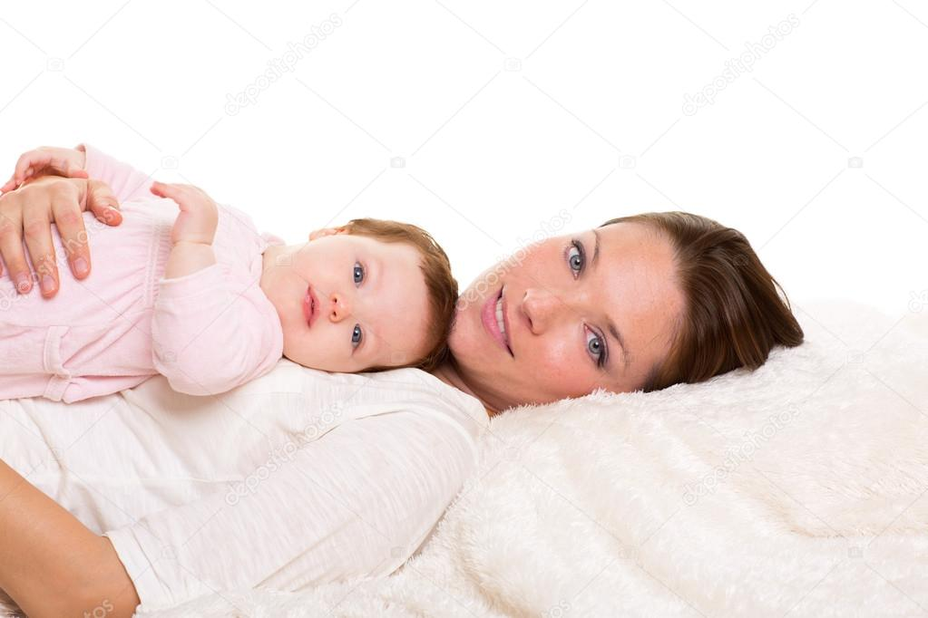 Baby girl and mother lying happy together on white fur blanket — Stock Photo #18432877