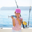 Child little girl fishing in boat holding little tunny fish catc — Stock Photo #19535577