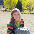 Kid little girl hoding halloween pumpkin in outdoor - Stock Photo