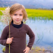 Blond kid girl outdoor holding spike in wetlands lake — Stock Photo #19536357