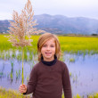 Blond kid girl outdoor holding spike in wetlands lake — Stock Photo #19536407