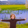 Blond kid girl outdoor holding spike in wetlands lake — Stock Photo #19536525