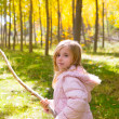 Stock Photo: Explorer girl with stick in poplar yellow autumn forest