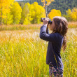 Explorer binocuar kid girl in yellow autumn nature — Stock Photo