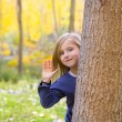 Autumn forest with child girl greeting hand in tree trunk - Stock Photo