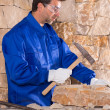 Masonry mason stonecutter man with hammer working - Stock Photo