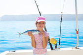Child little girl fishing in boat holding little tunny fish catc — Stock Photo