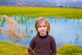 Blond kid girl outdoor holding spike in wetlands lake — Stock Photo