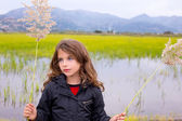 Brunette kid girl outdoor holding spike in wetlands lake — Stock Photo