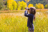 Explorer binocuar kid girl in yellow autumn nature — Stock fotografie