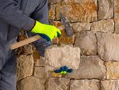Mason cantero con martillo y piedra de mampostería de trabajo — Foto de Stock