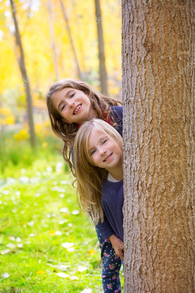 Autumn sister kid girls playing in poplar tree forest near trunk in nature outdoor — Stock Photo #19532995
