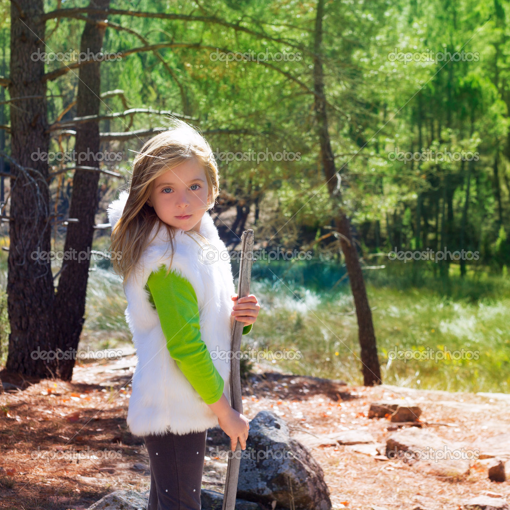 Explorer blond kid girl sith stick and winter white fur in pine forest ourdoor  Stock Photo #19535861