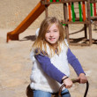 Blond child girl playing in playground smiling on swing — Stock Photo #19543767
