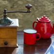 Retro old coffee grinder with vintage red teapot - Stock Photo