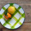 Fruits tangerine and pear in vintage porcelain dish plate - Stock Photo