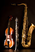 Music Sax tenor saxophone violin and clarinet in black — Stock Photo