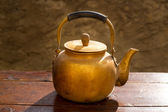Antique brass teapot on vintage wood table — Stock Photo