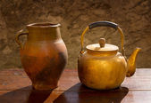 Antique brass teapot on retro wood table and clay jar — Stock Photo