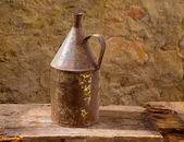 Antique rusted iron jar with aged brass on vintage wood — Stock Photo