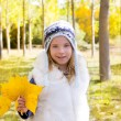 Child girl in autumn poplar forest yellow fall leaves in hand — Stock Photo